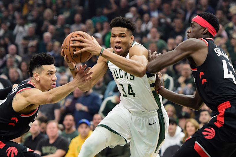Milwaukee Bucks forward Giannis Antetokounmpo (34) drives between Toronto Raptors guard Danny Green (14) and forward Pascal Siakam (43) during the first half of Game 2 of the NBA basketball playoffs Eastern Conference finals, Friday, May 17, 2019, in Milwaukee. (Frank Gunn/The Canadian Press via AP)