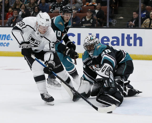 Los Angeles Kings right wing Carl Grundstrom, left, of Sweden, scores against Anaheim Ducks goaltender Ryan Miller, right, and right wing Corey Perry, center, during the first period of an NHL hockey game in Anaheim, Calif., Sunday, March 10, 2019. (AP Photo/Alex Gallardo)