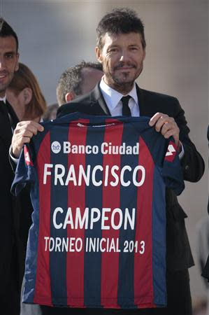A member of Argentine soccer team San Lorenzo shows the jersey they presented to Pope Francis during the Wednesday general audience in Saint Peter's square at the Vatican December 18, 2013. REUTERS/Tony Gentile