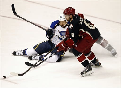St. Louis Blues' Chris Stewart (25) battles Phoenix Coyotes' David Schlemko (6) for the puck during the second period of an NHL hockey game, Friday, Dec. 23, 2011, in Glendale, Ariz. (AP Photo/Matt York)