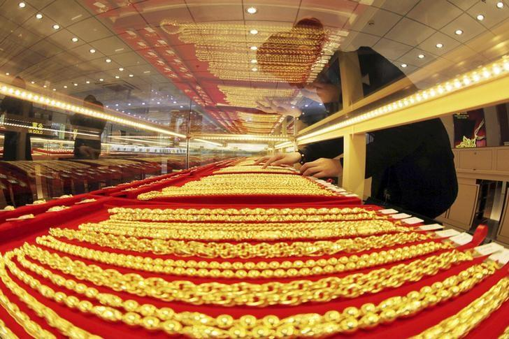 A sales assistant arranges gold necklaces at a store in Lianyungang
