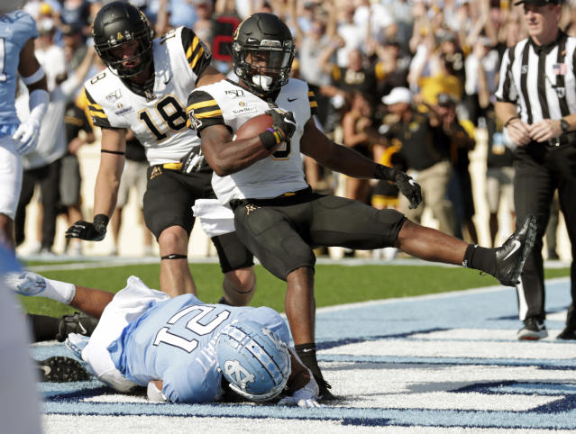 Appalachian State's Darrynton Evans (3) gets past North Carolina Tar Heels's Chazz Surratt (21) to score a touchdown during the first quarter of an NCAA college football game in Chapel Hill, N.C., Saturday, Sept. 21, 2019. (AP Photo/Chris Seward)