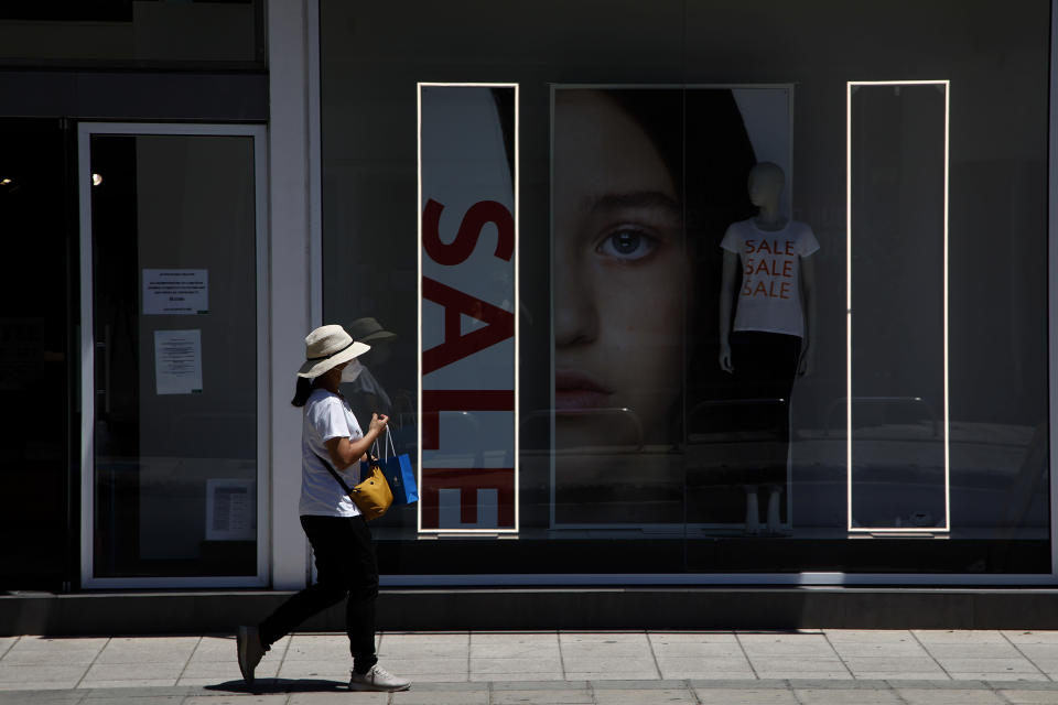 A woman wearing a face mask, walks outside of a shop at Makarios main shopping street in capital Nicosia, Cyprus, Friday, July 31, 2020. Cyprus has made mask-wearing compulsory in all indoor areas where people gather in large numbers like malls and supermarkets and is significantly ramping up random coronavirus testing at it's two main airports following an upsurge of new confirmed cases in the last week that has alarmed authorities. (AP Photo/Petros Karadjias)