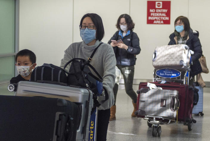 Airline passengers wearing face masks at the San Francisco International Airport. (Yichuan Cao/NurPhoto)