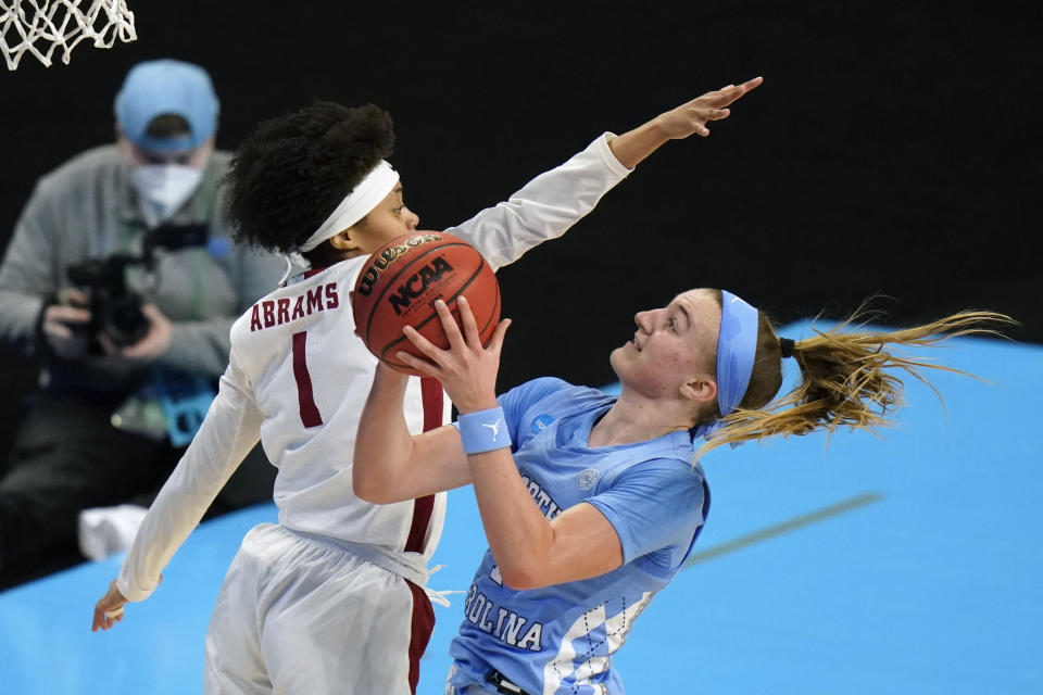 North Carolina guard Alyssa Ustby drives to the basket ahead of Alabama guard Megan Abrams, left, during the first half of a college basketball game in the first round of the women's NCAA tournament at the Alamodome in San Antonio, Monday, March 22, 2021. (AP Photo/Eric Gay)