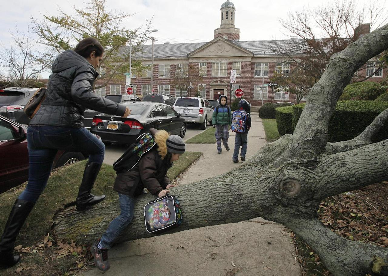 A woman and her son scramble over a tree toppled by Superstorm Sandy as she accompanies him to Public School 195, background, in the Manhattan Beach neighborhood of the Brooklyn borough, Monday, Nov. 5, 2012 in New York. Monday was the first day of public school for New York City students following the storm of a week ago. The woman declined to provide their names. (AP Photo/Mark Lennihan)