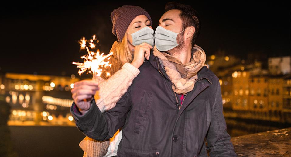 A kiss at new years eve midnight with a couple wearing masks