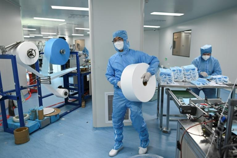 A worker wearing a protective suit makes masks at Naton Medical Group in Beijing