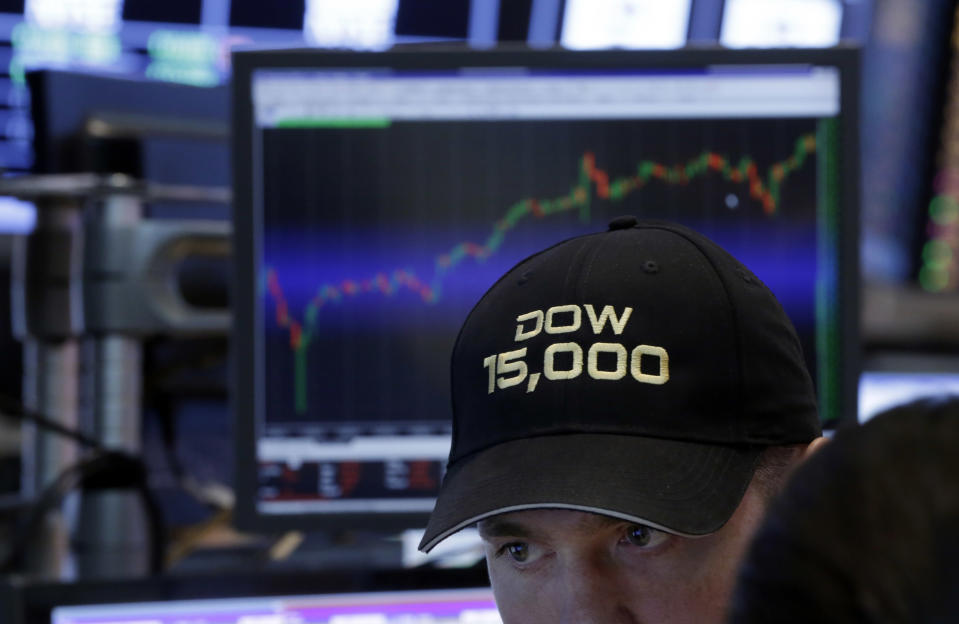 """FILE - In this Friday, May 3, 2013, file photo, a specialist wears a """"Dow 15,000"""" hat as he works at his post on the floor of the New York Stock Exchange, as a big gain in the job market is lifting the stock market to a record high. The stock market surged, traders donned party hats, and the wave of buying drove three indexes through major milestones in 2013. (AP Photo/Richard Drew, File)"""