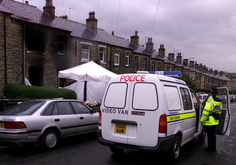 A police officer stands guard outside the house in Osborne Road, in the Birkby area of Huddersfield, West Yorkshire after the fire at the residence in 2002 (PA)