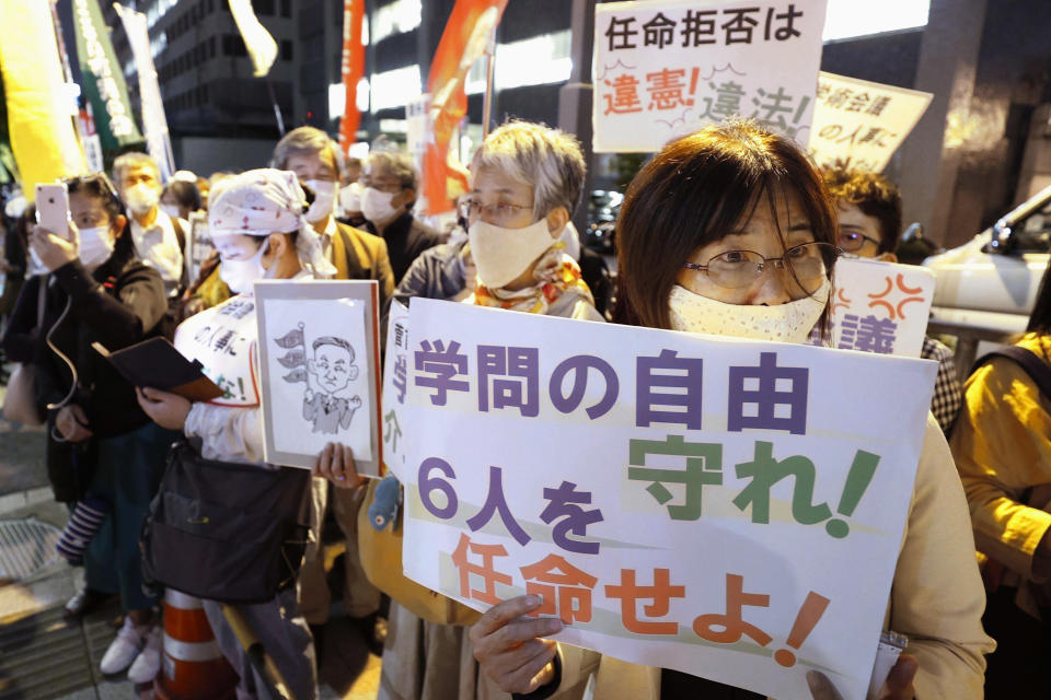 "People gather outside the prime minister's office in Tokyo on Oct. 6, 2020, during a protest against Japanese Prime Minister Yoshihide Suga's refusal, without explanation, to approve the appointments of six scholars to a government advisory body. This has drawn accusations that Suga is trying to muzzle dissent and impinge on academic freedoms. A sign, bottom right, reads ""Protect academic freedoms. Appoint the six scholars."" (Kyodo News via AP)"