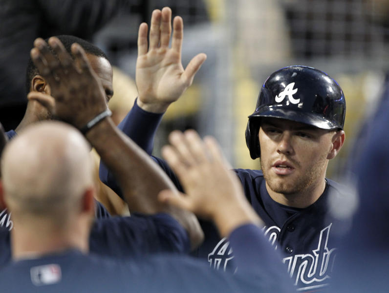 Atlanta Braves' Freddie Freeman, right, gets congratulations from teammates in the dugout after scoring on a single by Dan Uggla against the Los Angeles Dodgers in the fourth inning of a baseball game Friday, June 7, 2013, in Los Angeles. (AP Photo/Alex Gallardo)