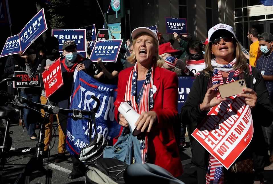 """People hold signs reading """"Trump 2020,"""" """"Trump Pence"""" and """"Voting ends on election day, not the day after."""""""