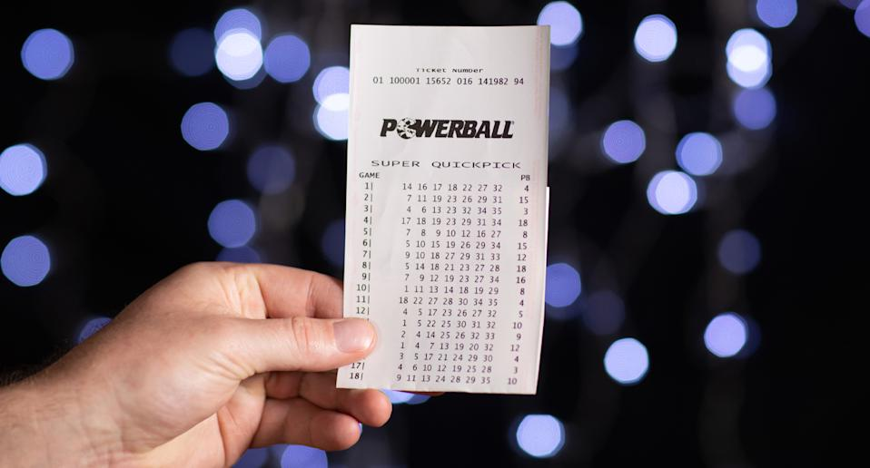 Pictured is a man's hand holding a Powerball Super Quickpick ticket.