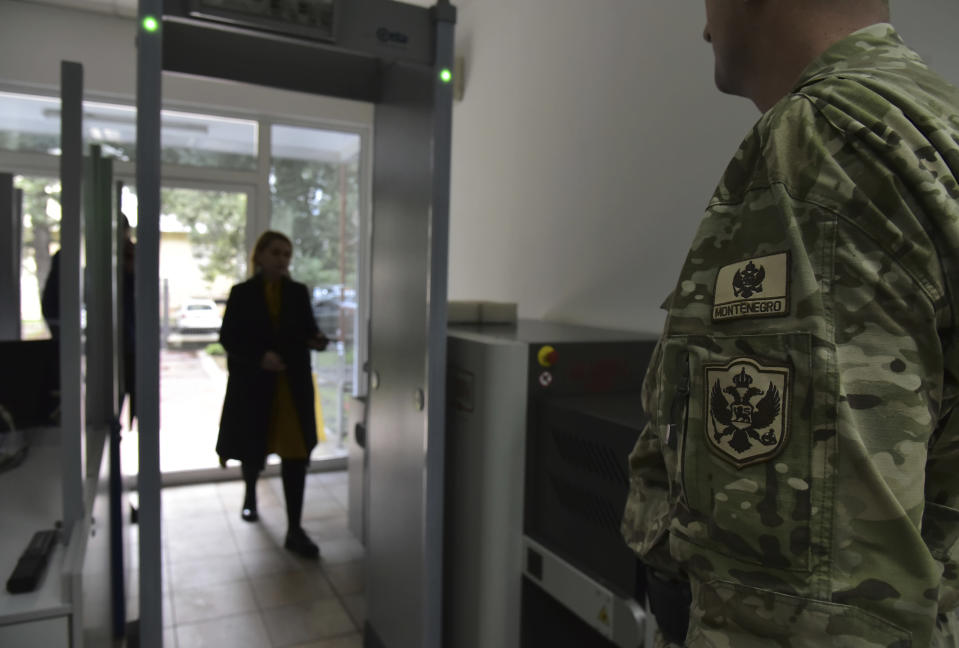 In this photo taken Monday, Nov. 11, 2019, a guard stands at the entrance of the Montenegrin Defense Ministry in Montenegro's capital Podgorica. Deployed inside the sprawling communist-era army command headquarters in Montenegro's capital, a group of elite U.S. military cyber experts are plotting strategy in a fight against potential Russian and other cyberattacks ahead of the 2020 American and Montenegrin elections. (AP Photo/Risto Bozovic)