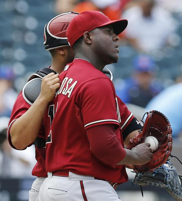 Arizona Diamondbacks catcher Welington Castillo (7) consoles Diamondbacks starting pitcher Rubby De La Rosa (12) in the third inning of a baseball game against the New York Mets in New York, Sunday, July 12, 2015. (AP Photo/Kathy Willens)