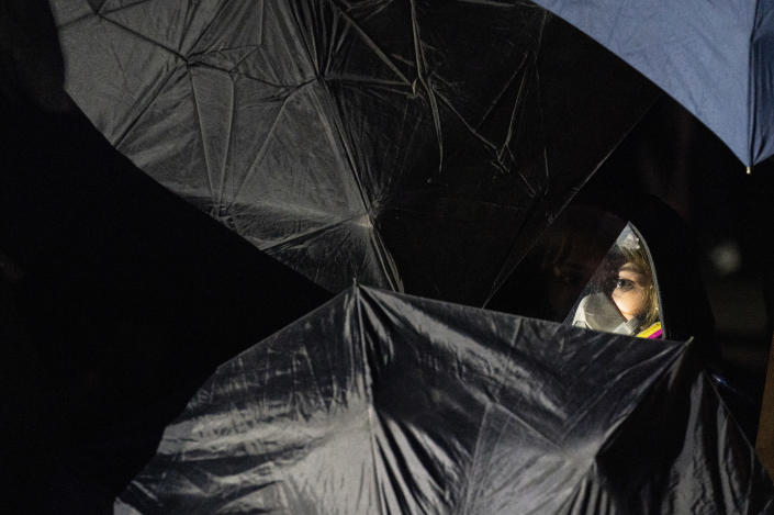 A demonstrator hides behind a phalanx of umbrellas before advancing on a perimeter security fence to agitate authorities during a protest decrying the shooting death of Daunte Wright outside the Brooklyn Center Police Department, Wednesday, April 14, 2021, in Brooklyn Center, Minn. (AP Photo/John Minchillo)