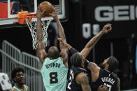 Charlotte Hornets center Bismack Biyombo (8) dunks the ball while guarded by Los Angeles Clippers forward Kawhi Leonard (2) and guard Paul George (13) during the first half of an NBA basketball game in Charlotte, N.C., Thursday, May 13, 2021. (AP Photo/Jacob Kupferman)