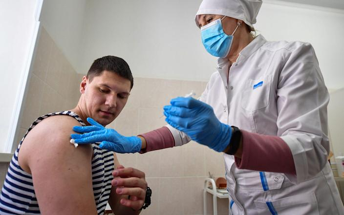 A student of the Makarov Pacific Higher Naval School is vaccinated with the first component of the Gam-COVID-Vac (Sputnik V) COVID-19 vaccine - Yuri Smityuk/TASS