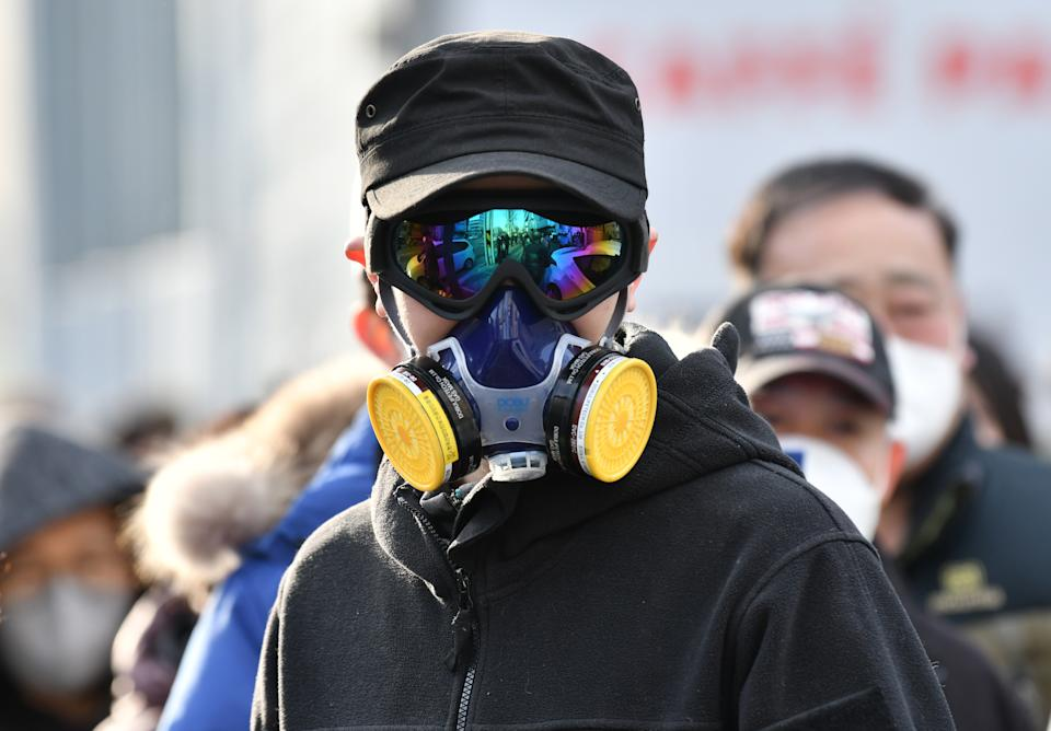 A man wears a mask and goggles as he waits in line to buy face masks from a post office near the Daegu branch of the Shincheonji Church of Jesus in Daegu on February 27, 2020. - The secretive South Korean religious group at the centre of the country's new coronavirus outbreak is a sprawling network so wealthy it can mobilise thousands of believers to hold Pyongyang-style mass performances at Seoul's Olympic stadium. More than half of the country's nearly 1,600 infections are linked to Shincheonji followers. (Photo by Jung Yeon-je / AFP) (Photo by JUNG YEON-JE/AFP via Getty Images)