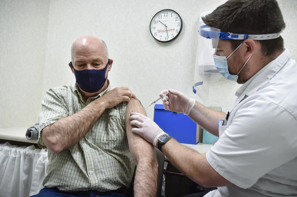 """FILE - In this April 1, 2021 file photo, Montana Gov. Greg Gianforte receives a shot of the Pfizer COVID-19 vaccine from pharmacist Drew Garton at a Walgreen's pharmacy in Helena, Mont. While large companies across the U.S. have announced that the COVID-19 vaccine will be required for their employees to return to work in-person, there is one state where such requirements are banned: Montana. Under a new law passed by the Republican-controlled Montana Legislature earlier this year, requiring vaccines as a condition for employment is deemed """"discrimination"""" and a violation of the state's human rights laws.(Thom Bridge/Independent Record via AP, File)"""