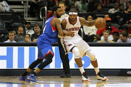 Atlanta Hawks small forward Josh Smith (5) drives to the basket as Philadelphia 76ers small forward Dorell Wright (4) defends in second half action of an NBA basketball game on Wednesday, March 6, 2013, in Atlanta. The Hawks won the game 107-96. (AP Photo/Todd Kirkland)
