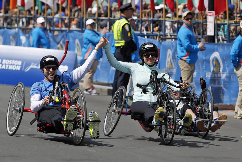 Boston Marathon husband and wife bombing survivors Patrick Downes and Jessica Kensky, who each lost a leg in last year's bombings, roll across the finish line in the 118th Boston Marathon Monday, April 21, 2014 in Boston. (AP Photo/Elise Amendola)