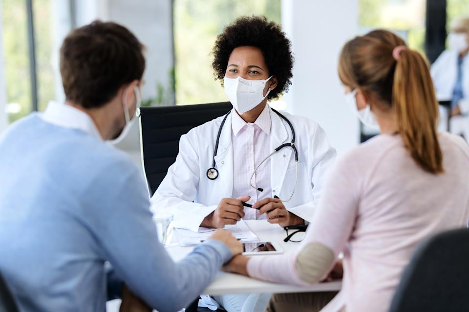 Black female doctor talking to a couple while wearing protective face mask during counseling at doctor's office.