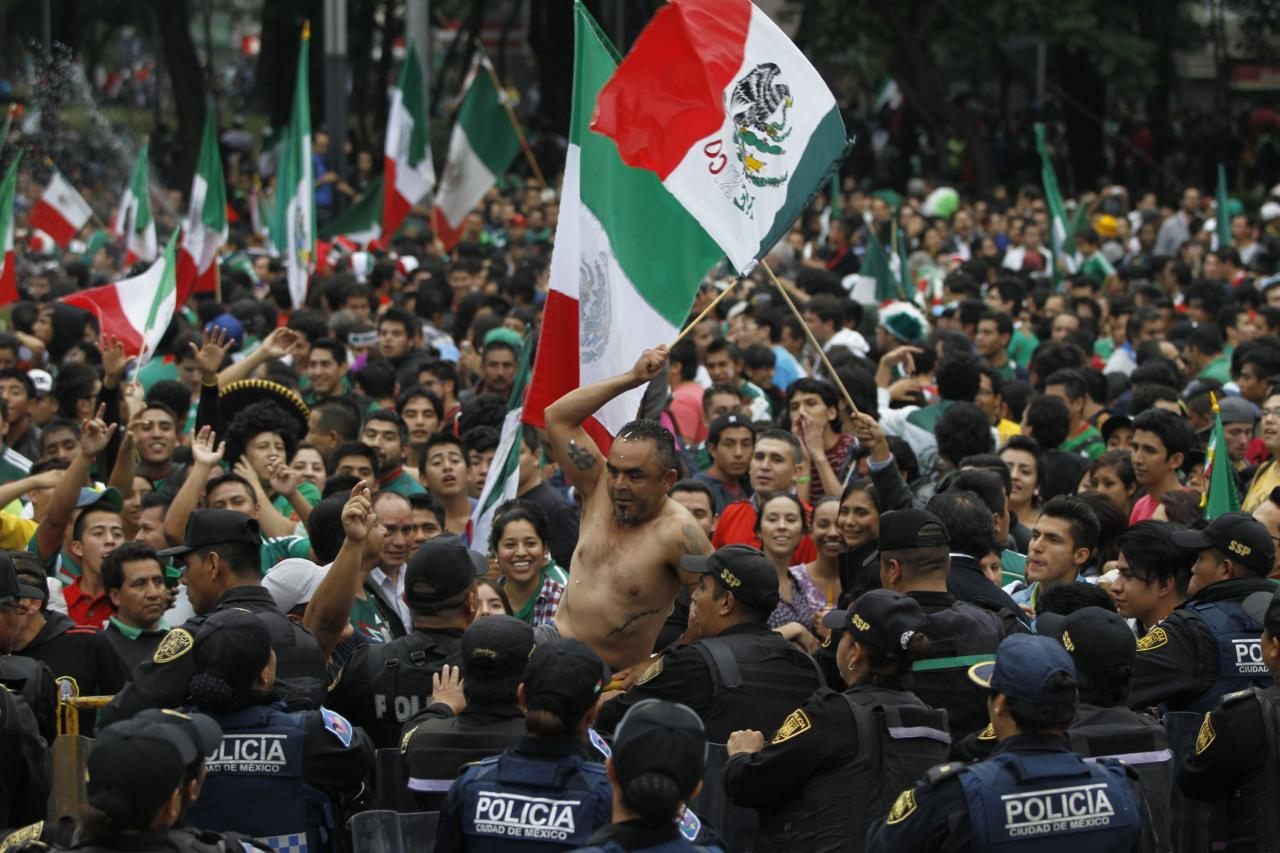 Mexican soccer fans celebrate in front of police after Mexico beat Croatia in their 2014 World Cup match, at the Angel of Independence monument in Mexico City June 23, 2014. REUTERS/Carlos Jasso (MEXICO - Tags: SOCIETY SPORT SOCCER WORLD CUP)