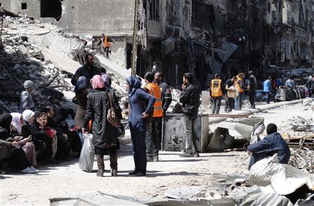 Residents wait to receive food aid distributed by the Al-Wafaa campaign at the besieged al-Yarmouk camp, south of Damascus April 1, 2014. REUTERS/Rame Alsayed