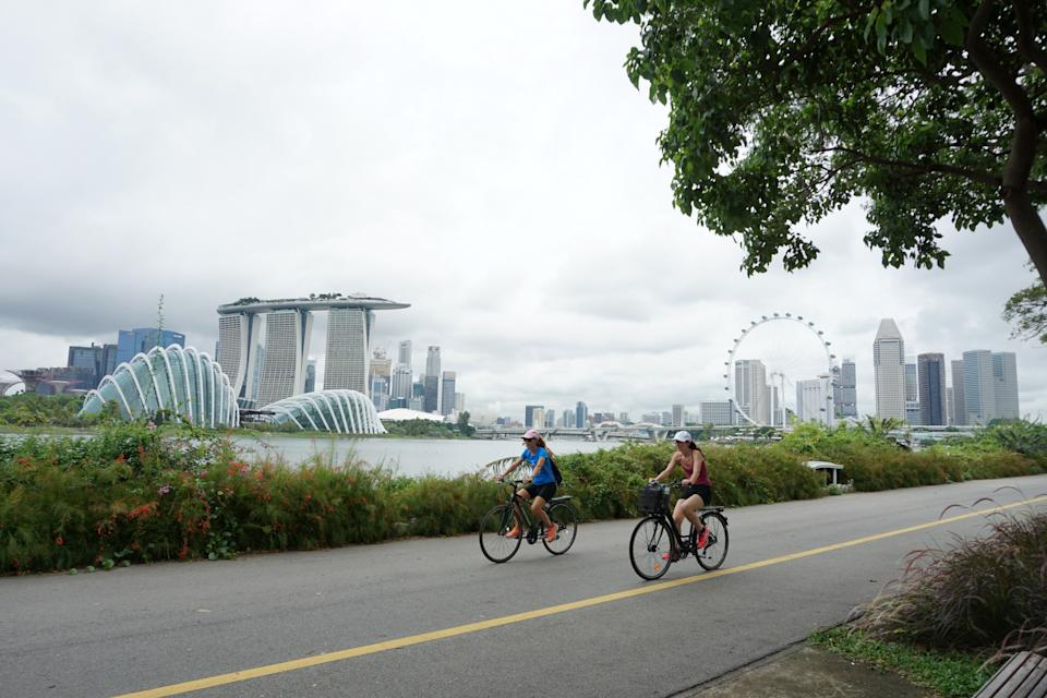 Cyclists ride along Marina Bay overlooking the financial business district in Singapore on July 14, 2020. - Singapore plunged into recession in the second quarter as the economy contracted more than 40 percent, preliminary data showed on July 14, with the trade-dependent city state hammered by the coronavirus in another ominous sign for the global recovery. (Photo by Roslan RAHMAN / AFP) (Photo by ROSLAN RAHMAN/AFP via Getty Images)