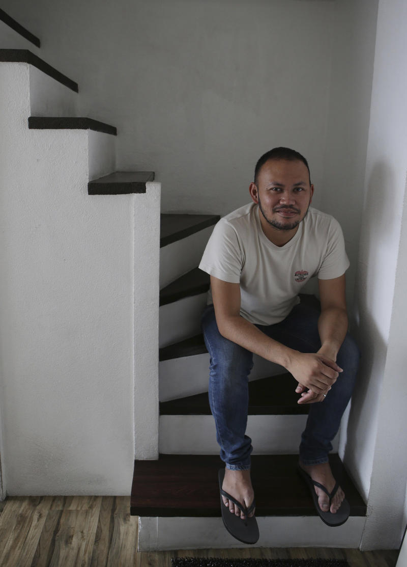 """In this May 8, 2013 photo, Filipino director Borinaga Alix Jr. poses inside his home in suburban Quezon city, north of Manila, Philippines. Alix chose to film """"Death March"""" in black-and-white and almost entirely inside a studio using hand-painted backdrops, with close-ups of actors' painted faces portraying their struggles with nightmares and hallucinations in one of the bloodiest episodes of World War II. (AP Photo/Aaron Favila)"""