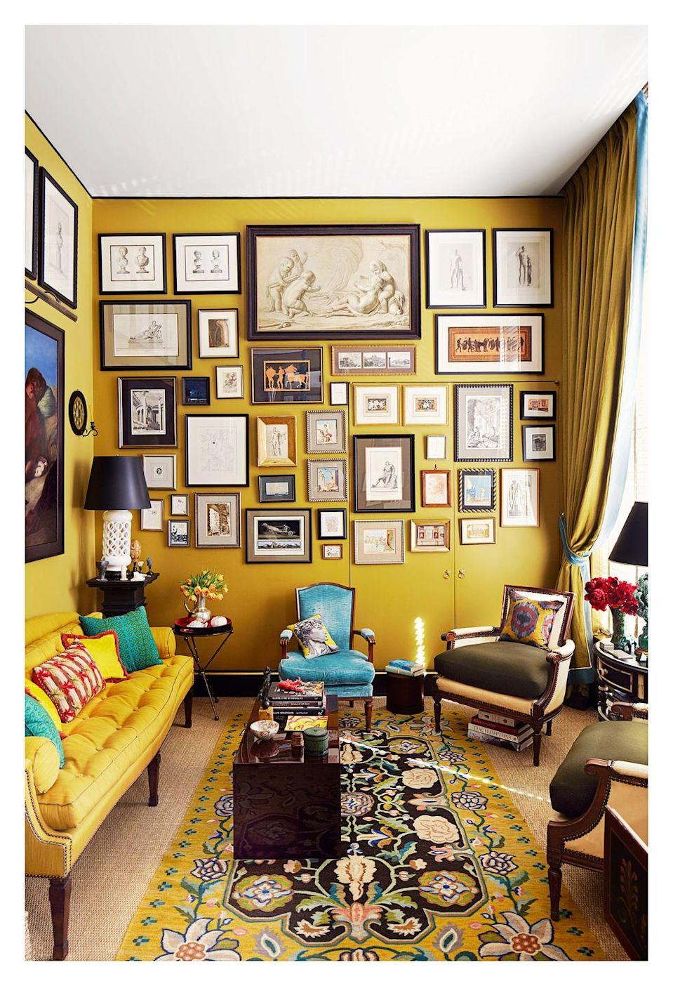 """<p>Before we even comment on paint color, can we just take a moment to appreciate that wild gallery? This marigold living room designed by <a href=""""https://brockschmidtandcoleman.com/"""" rel=""""nofollow noopener"""" target=""""_blank"""" data-ylk=""""slk:Brockschmidt & Coleman"""" class=""""link rapid-noclick-resp"""">Brockschmidt & Coleman</a> is at once classic and quirky, unique and timeless. The walls are covered in <a href=""""https://www.benjaminmoore.com/en-us/color-overview/find-your-color/color/2151-10/mustard-olive?color=2151-10"""" rel=""""nofollow noopener"""" target=""""_blank"""" data-ylk=""""slk:Mustard Olive by Benajmin Moore"""" class=""""link rapid-noclick-resp"""">Mustard Olive by Benajmin Moore</a> and bordered at the ceiling in black. </p>"""