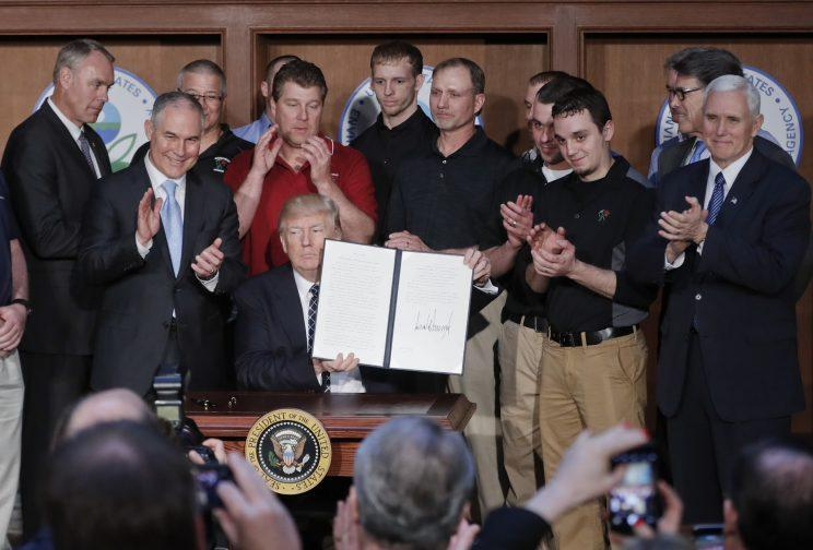 President Trump, seated, accompanied by coal miners and, from left, Interior Secretary Ryan Zinke, Environmental Protection Agency (EPA) Administrator Scott Pruitt, second from right, Energy Secretary Rick Perry, and Vice President Mike Pence, far right, holds up the signed Energy Independence Executive Order on March 28, 2017, at EPA headquarters in Washington. (Photo: Pablo Martinez Monsivais/AP)
