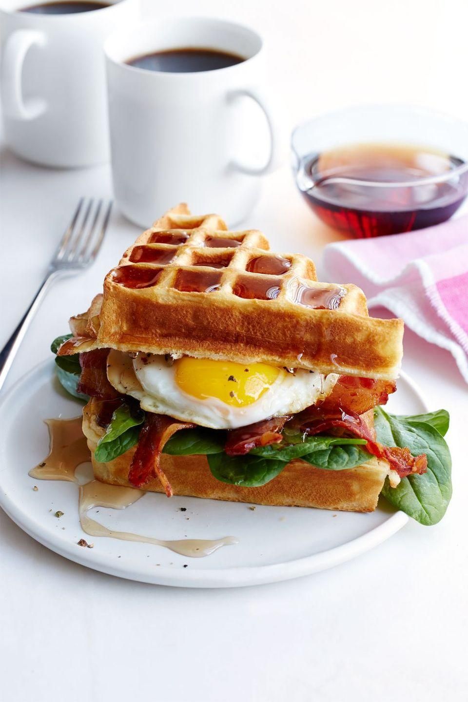 "<p>Sweet-savory fans, unite! This knockout brunch combines waffles with eggs and bacon and a generous drizzle of maple syrup.</p><p><em><a href=""https://www.womansday.com/food-recipes/recipes/a50558/buttermilk-waffle-bacon-egg-sandwich-recipe-wdy0615/"" rel=""nofollow noopener"" target=""_blank"" data-ylk=""slk:Get the recipe from Woman's Day »"" class=""link rapid-noclick-resp"">Get the recipe from Woman's Day »</a></em></p>"