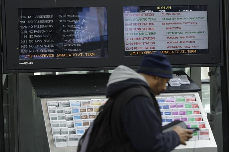 A commuter walks past monitors showing limited service at the Long Island Rail Road Jamaica Station Thursday, Nov. 1, 2012, in the New York City borough of Queens. Three days after superstorm Sandy made landfall, residents and commuters still faced obstacles as they tried to return to pre-storm routines. (AP Photo/Frank Franklin II)