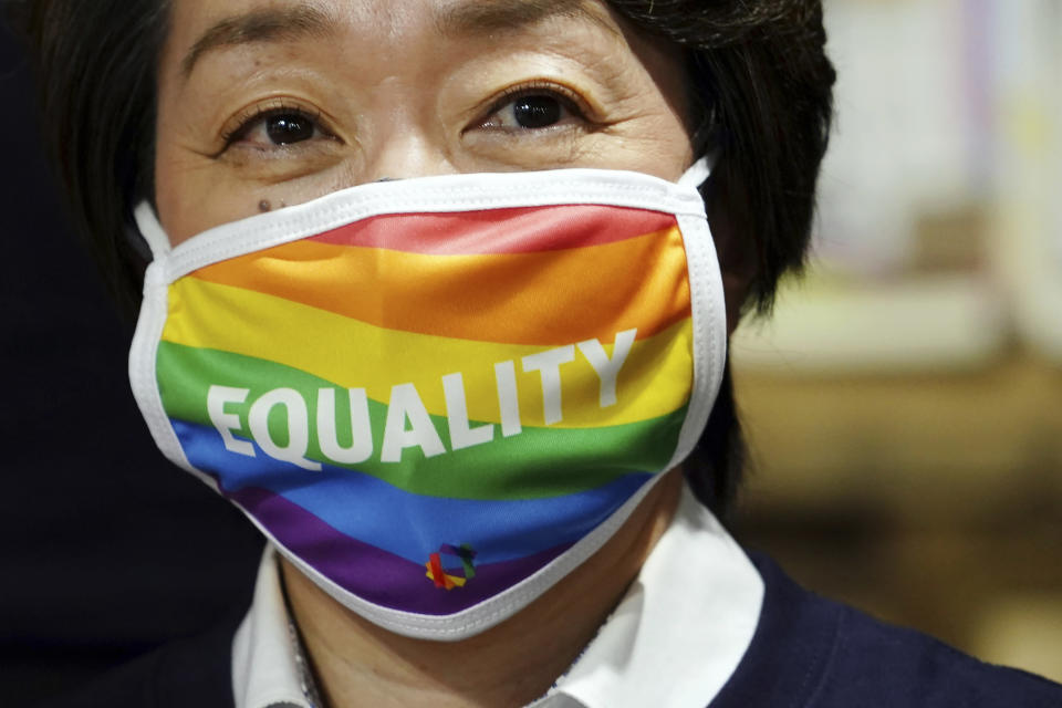 """Tokyo 2020 Organizing Committee President Seiko Hashimoto wearing a rainbow-colored mask with word """"Equality"""" visits Pride House Tokyo Legacy in Tokyo Tuesday, April 27, 2021. Japan marked LGBTQ week with pledge to push for equality law before the Olympics. (AP Photo/Eugene Hoshiko, Pool)"""