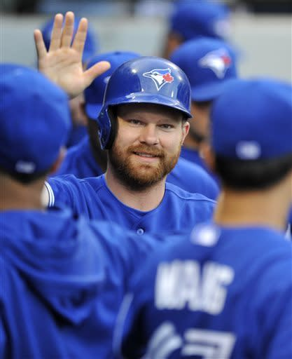 Toronto Blue Jays' Adam Lind celebrates in the dugout after scoring on a Maicer Izturis single during the second inning of a baseball game against the Chicago White Sox in Chicago, Tuesday, June 11, 2013. (AP Photo/Paul Beaty)