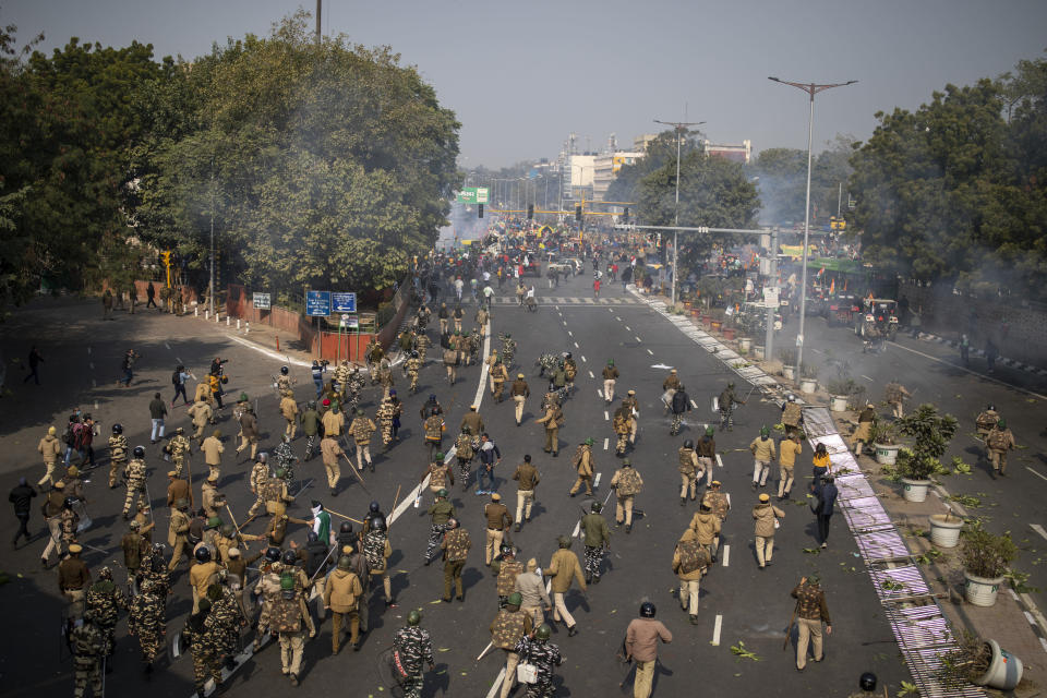 Indian police chase protesting farmers away as they march to the capital breaking police barricades during India's Republic Day celebrations in New Delhi, India, Tuesday, Jan. 26, 2021. Tens of thousands of farmers drove a convoy of tractors into the Indian capital as the nation celebrated Republic Day on Tuesday in the backdrop of agricultural protests that have grown into a rebellion and rattled the government. (AP Photo/Altaf Qadri)