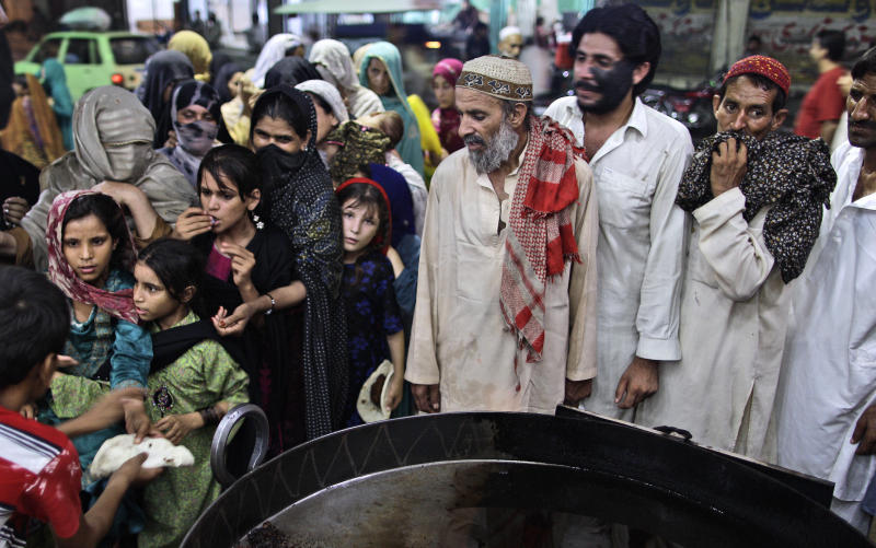 In this Tuesday, July 31, 2012 photo, Pakistanis wait to receive a donated meal during the Muslim holy fasting month of Ramadan, at a restaurant in Rawalpindi, Pakistan. For many years, Pakistan required all Sunni Muslims, who make up a majority of the country's population, to pay zakat to the government. That regulation changed recently, but many Pakistanis seem unaware and continue to pull their money out of the bank to elude the state. (AP Photo/Muhammed Muheisen)