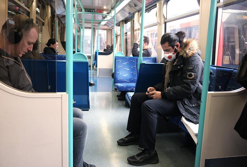 A passenger wearing a mask on a DLR train heading toward Canary Wharf, London, the day after Prime Minister Boris Johnson called on people to stay away from pubs, clubs and theatres, work from home if possible and avoid all non-essential contacts and travel in order to reduce the impact of the coronavirus pandemic.