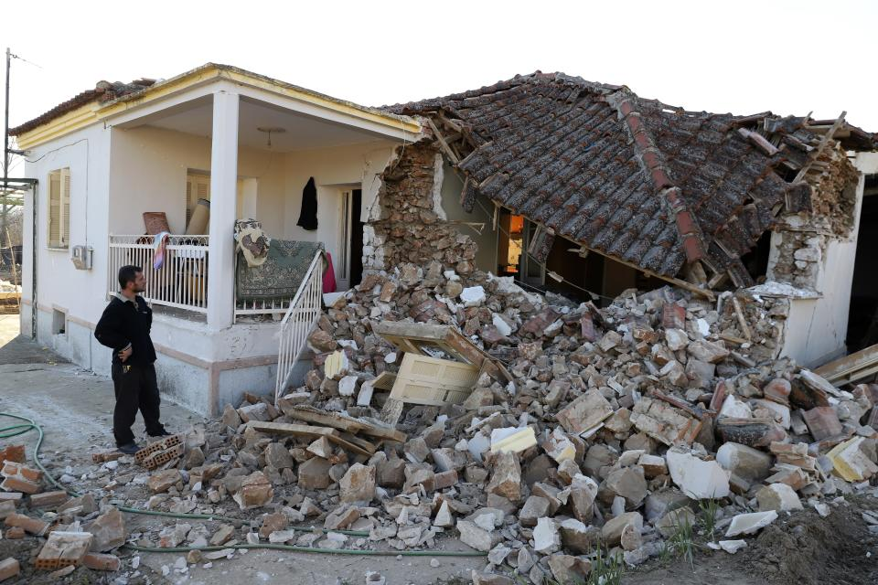A man stands next to a damaged house after an earthquake in Mesochori village, central Greece, Wednesday, March 3, 2021. An earthquake with a preliminary magnitude of at least 6.0 struck central Greece Wednesday and was also felt in neighboring Albania and North Macedonia, and as far as Kosovo and Montenegro. (AP Photo/Vaggelis Kousioras)