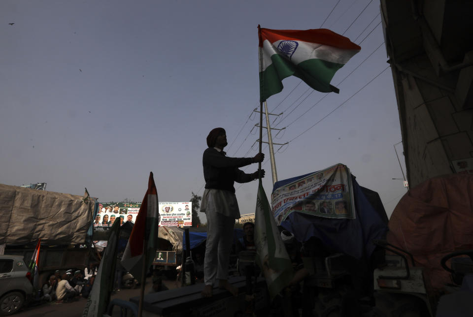 An Indian farmer erects the Indian flag after arriving at the Delhi-Uttar Pradesh border for Tuesday's tractor rally in New Delhi, India, Monday, Jan. 25, 2021. Thousands of farmers gathered on the borders of Delhi for a massive tractor rally on Tuesday against the three contentious farm laws when India will celebrate its Republic day with a military and cultural parade. The two-month-old old blockade of highways connecting the capital with the country's north continues as the talks have remained deadlocked with the government refusing to scrap the new agricultural reform laws which the farmers say will benefit large corporations. (AP Photo/Manish Swarup)