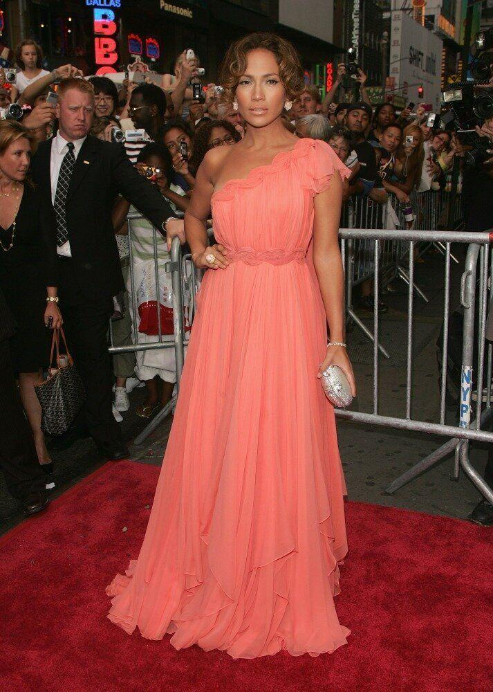 Actress Jennifer Lopez wears a one-shoulder coral pink gown.
