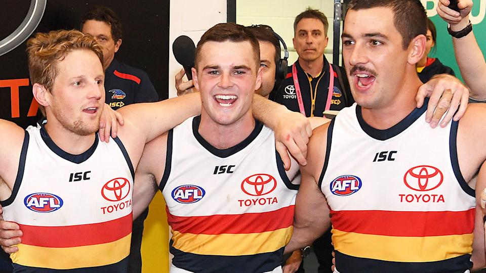 Pictured in the centre, Brad Crouch celebrates after a game with Adelaide Crows teammates.