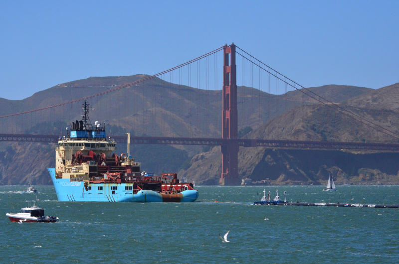 FILE- In this Sept. 8, 2018 file photo, a ship tows The Ocean Cleanup's first buoyant trash-collecting device toward the Golden Gate Bridge in San Francisco en route to the Pacific Ocean. A trash collection device deployed to corral plastic litter floating between California and Hawaii will be hauled back to dry land for repairs. Boyan Slat, who launched the Pacific Ocean cleanup project, tells NBC the 2,000-foot (600-meter) long floating boom will be towed to Hawaii. If it can't be repaired there it will be loaded on a barge and returned to its home port of Alameda, Calif. The boom broke apart under constant wind and waves. Slat says he's disappointed, but not discouraged. (AP Photo/Lorin Eleni Gill, File)