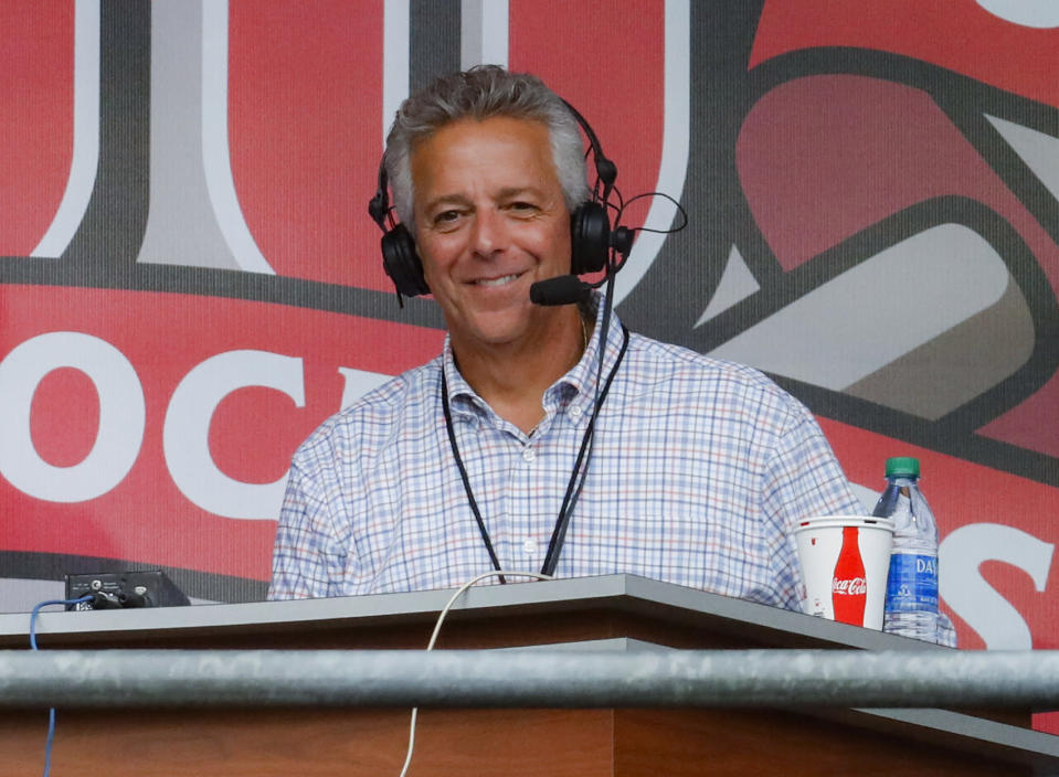 FILE - In this Sept. 25, 2019, file photo, Cincinnati Reds broadcaster Thom Brennaman sits in a special outside booth before the Reds' baseball game against the Milwaukee Brewers in Cincinnati. Brennaman, who used a homophobic slur while broadcasting the first game of a doubleheader, apparently not realizing he was on the air. Right in the middle of calling the second game, he apologized for his hateful language and was removed from the telecast. (AP Photo/John Minchillo, File)