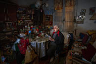 Francisca Cano Vila, 80, watches television while eating a yogurt for Christmas Eve dinner at her home in Barcelona, Spain, Thursday, Dec. 24, 2020. Many of Barcelona's elderly poor who live alone feel more isolated than ever on a Christmas Eve without family or friends due to pandemic restrictions in Spain. For these seniors, the night before Christmas will consist of a yogurt or a cold sandwich without more company than, perhaps, the television. (AP Photo/Emilio Morenatti)