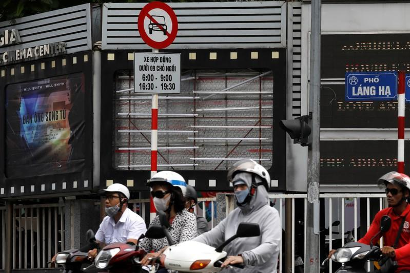 "FILE PHOTO: Bikers drive past an empty space where a promotional poster for the DreamWorks film ""Abominable"" was hanging before being taken down at a cinema in Hanoi"