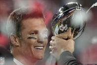 Tampa Bay Buccaneers quarterback Tom Brady looks at the Vince Lombardi trophy after defeating the Kansas City Chiefs in the NFL Super Bowl 55 football game Sunday, Feb. 7, 2021, in Tampa, Fla. The Buccaneers defeated the Chiefs 31-9 to win the Super Bowl. (AP Photo/David J. Phillip)